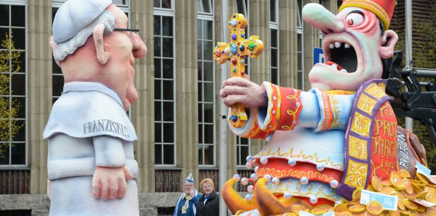 <p>A figure of Argentinian Pope Francis of the Catholic Church (L) and a swank figure of the church holding a cross are pictured during the traditional Rose Monday parade on March 3, 2014 in Duesseldorf, western Germany. Carnival goers mainly in the Rhine region traditionally celebrate the highlight procession on Rosenmontag (Rose Monday).  AFP PHOTO / PATRIK STOLLARZ        (Photo credit should read PATRIK STOLLARZ/AFP/Getty Images)</p>