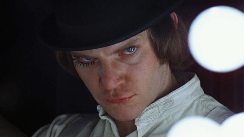 primo piano del protagonista del film arancia meccanica con cilindro e ciglia lunghe su occhio destro